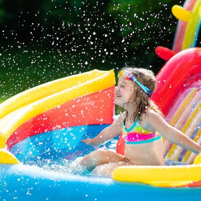 滑り台付きのビニールプールで遊ぶ女の子