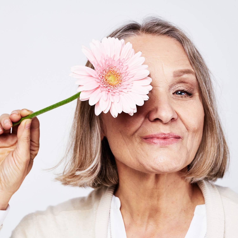 顔の近くに花を持つ年配の女性